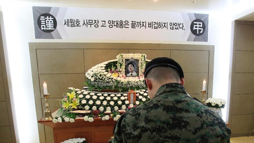 "In this May 16, 2014 photo, a South Korean army soldier pays a silent tribute during a memorial service for sunken ferry Sewol chief officer Yang Dae-hong, a hero, in Incheon, South Korea. In his last phone call to his wife while the ship was sinking, Yang told her where to find savings for their teenage children's college tuition and hung up saying he had to go save students. His body was found one month after the accident. His brother said his face was unrecognizable and his walkie-talkie was found along with his body. The banner at top reads: ""Sewol ferry chief officer Yang Dae-hong was not a coward to the end."" (AP Photo/Ahn Young-joon)"