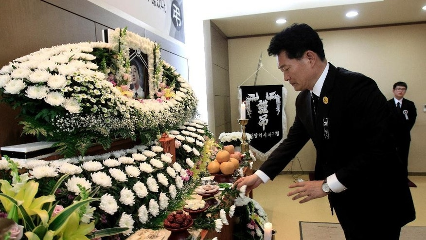 In this May 16, 2014 photo, Incheon Mayor Song Young-gil places a flower at the altar during a memorial service for sunken South Korean ferry Sewol chief officer Yang Dae-hong, a hero, in Incheon, South Korea. In his last phone call to his wife while the ship was sinking, Yang told her where to find savings for their children's college tuition, then said he had to go save students and hung up. Survivors said the 45-year-old returned to the sinking ship after helping them escape to safety.  (AP Photo/Ahn Young-joon)