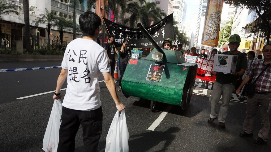 "A protester stands in front of a mock tank to symbolize the man blocking a line of tanks at the 1989 pro-democracy movement in Beijing, as thousands of Hong Kong people march on a downtown street in Hong Kong Sunday, June 1, 2014, to mark the 25th anniversary of China's bloody crackdown on Tiananmen Square on June 4, ahead of a much larger annual candlelight vigil. The Chinese words on white T-shirt reads "" Citizen against orders. "" (AP Photo/Vincent Yu)"