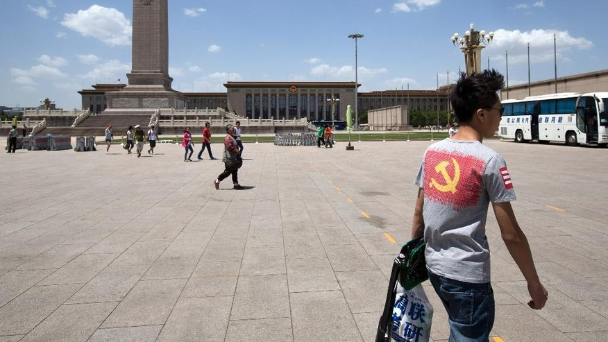 In this May 27, 2014 photo, a teenage tourist, right, wears a t-shirt displaying a logo of the Chinese Communist Party as he visits Tiananmen Square in Beijing. A quarter century after the Communist Party's attack on demonstrations centered on Tiananmen Square on June 4, 1989, it is little more than a distant tale to young Chinese. The ruling party prohibits public discussion and 1989 is banned from textbooks and Chinese websites. (AP Photo/Alexander F. Yuan)