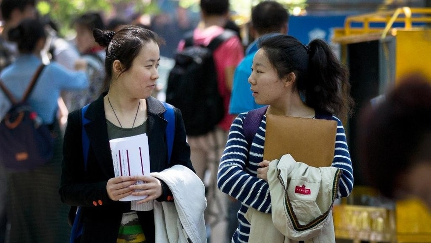 In this May 7, 2014 photo, Wang Jiaying, left, chats with Lu Qiuxuan as they walk out from their university in Beijing, China. A quarter century after the Communist Party's attack on demonstrations centered on Tiananmen Square on June 4, 1989, it is little more than a distant tale to young Chinese. The ruling party prohibits public discussion and 1989 is banned from textbooks and Chinese websites. (AP Photo/Andy Wong)
