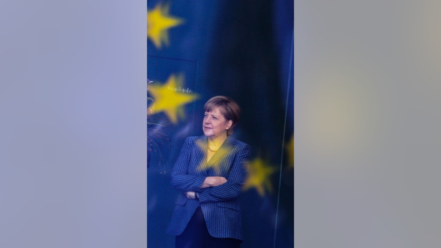 German Chancellor Angela Merkel stands behind a window with the reflection of a European flag as she waits for the arrival of Georgia's Prime Minister Irakli Garibashvili for talks at the chancellery in Berlin, Monday, June 2, 2014. (AP Photo/Markus Schreiber),