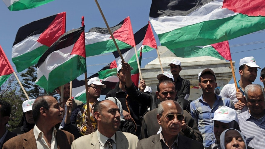 April 22, 2014 - FILE photo of Palestinians waving national flags during a rally to demand the end of Palestinian political divisions, at the main square of Gaza City. Propelled by crises, rivals Hamas and Fatah are moving toward forming a unity government, in what appears to be their most promising attempt yet to end a 7-year rift that weakened the Palestinian case for statehood.