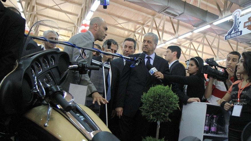 ADVANCE  FOR STORY SLUGGED ALGERIA CLOSED ECONOMY BY PAUL SCHEMM. In this photo dated June 28, 2014, Algerian Prime Minister, Abdelmalek Sellal, center, visits the American pavilion at the International Trade Fair in the Algerian capital, Algiers. A Harley-Davidson motorcycle is displayed on foreground. Prime Minister Abdelmalek Sellal said over the weekend that the government intends to encourage more foreign interest in the under performing agriculture, industry and tourism sectors. Algeria still has a positive balance of trade and hefty foreign reserves of $190 billion, but its energy production has been in decline since 2005 and analysts warn the country will eventually run out of money if it doesn't change its profligate ways. (AP Photo)