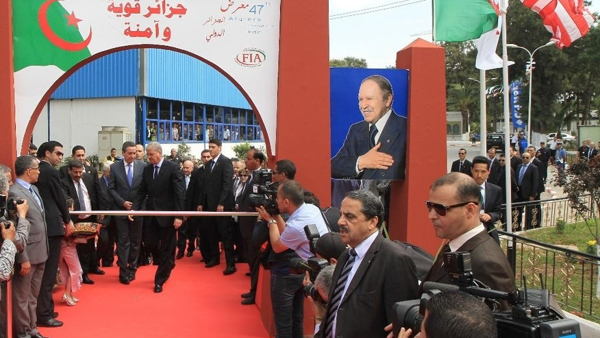 In this photo dated May 28, 2014, Algerian Prime Minister, Abdelmalek Sellal, center, inaugurates the International Trade Fair in the Algerian capital, Algiers. Prime Minister Abdelmalek Sellal said over the weekend that the government intends to encourage more foreign interest in the under performing agriculture, industry and tourism sectors. Algeria still has a positive balance of trade and hefty foreign reserves of $190 billion, but its energy production has been in decline since 2005 and analysts warn the country will eventually run out of money if it doesn't change its profligate ways. (AP Photo)