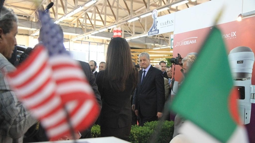 In this photo dated May 28, 2014, Algerian Prime Minister, Abdelmalek Sellal, cente right, visits the American pavilion at the International Trade Fair in the Algerian capital, Algiers. Prime Minister Abdelmalek Sellal said over the weekend that the government intends to encourage more foreign interest in the under performing agriculture, industry and tourism sectors. Algeria still has a positive balance of trade and hefty foreign reserves of $190 billion, but its energy production has been in decline since 2005 and analysts warn the country will eventually run out of money if it doesn't change its profligate ways.(AP Photo)