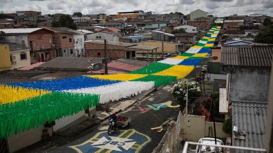 In this May 21, 2014 photo, a man rides his motorbike under a canopy of ribbons through a street decorated in honor of the upcoming 2014 World Cup, in Manaus, Brazil. While the forest fauna is largely absent from the metropolis itself, nature makes itself felt in the hothouse climate and the blooms of mold that envelop the low-slung concrete buildings. Humidity hovers around 80 percent year-round. (AP Photo/Felipe Dana)
