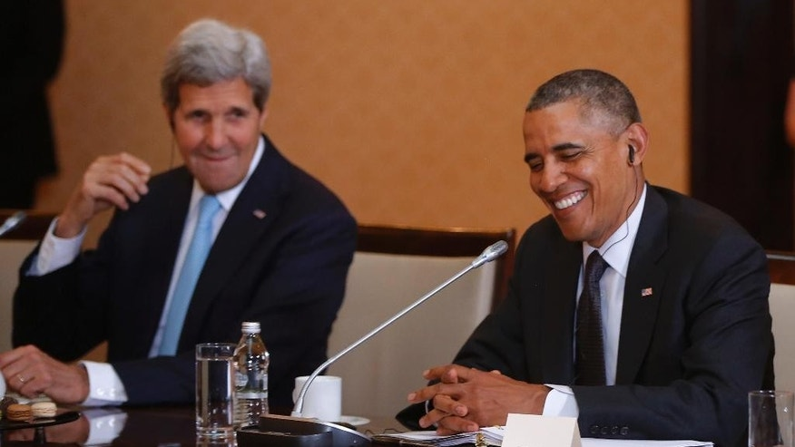 U.S. President Barack Obama, right, and Secretary of State John Kerry smile during their bilateral meeting with Poland's Prime Minister Donald Tusk in Warsaw, Poland, Tuesday, June 3, 2014 (AP Photo/Charles Dharapak)