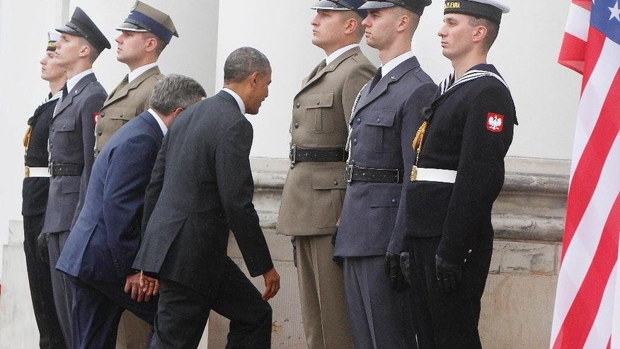 Polish President Bronislaw Komorowski and US President Barack Obama, center, are on their way into the Belvedere Palace  in Warsaw, Poland, on Tuesday June 3, 2014. Obama came to Poland to meet regional leaders and attend ceremonies marking 25 years of Poland's democracy.(AP Photo/Czarek Sokolowski)