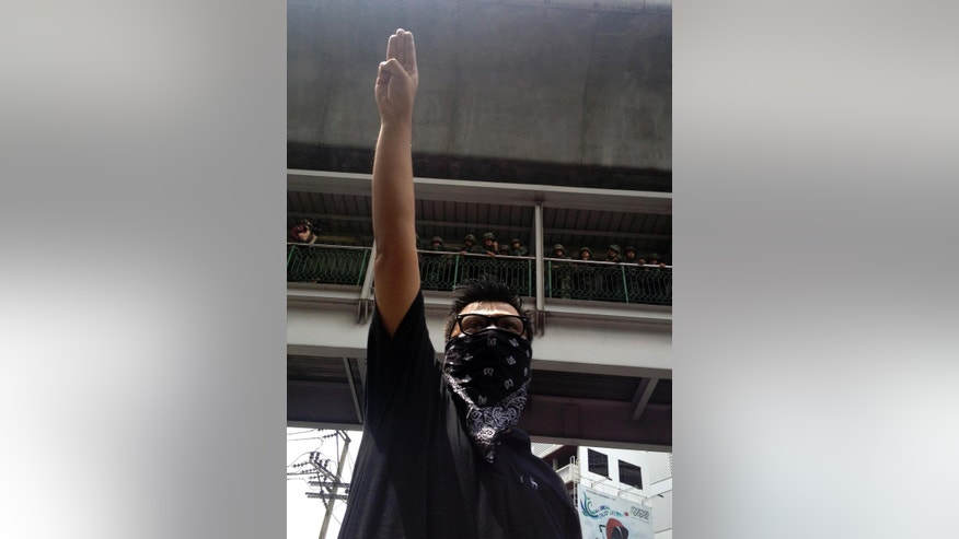 June 1, 2014: In this photo, an anti-coup protester gives a three-finger salute as soldiers keep eyes on him from an elevated walkway near a rally site in central Bangkok, Thailand.