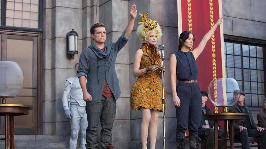 "This image released by Lionsgate shows, from left,  Josh Hutcherson as Peeta Mellark, Elizabeth Banks as Effie Trinket and Jennifer Lawrence as Katniss Everdeen in a scene from the film, ""The Hunger Games: Catching Fire."" A fictional gesture from a Hollywood movie is being used as a real symbol of resistance in Thailand."