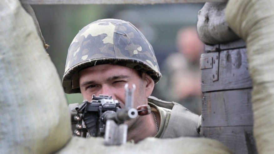 June 3, 2014: A Ukrainian soldier takes position as he patrols an area, close to Slovyansk, Ukraine. Ukrainian troops on Tuesday launched an offensive against pro-Russian insurgents in the eastern city of Slovyansk and advanced through the city's outskirts, the nation's interior minister said.