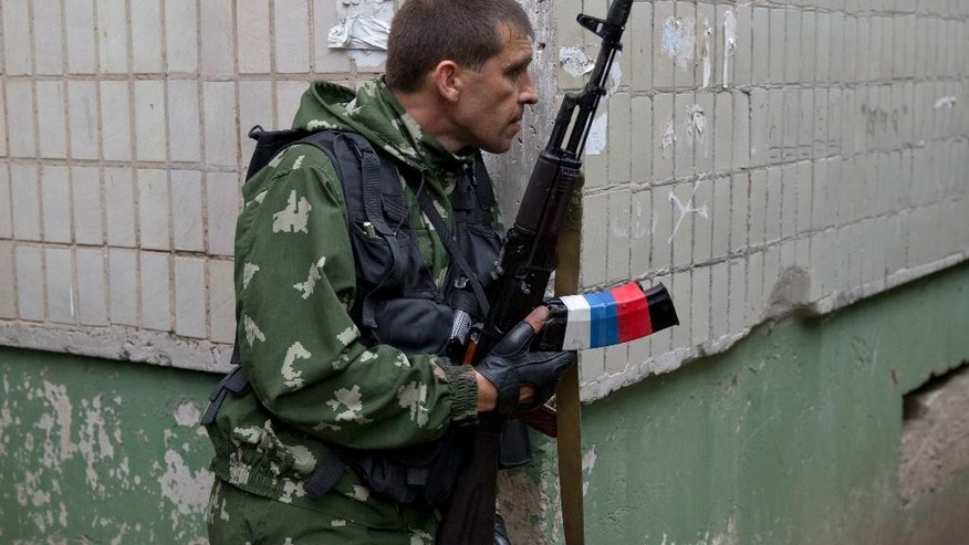 A pro-Russian holds his weapon during clashes with Ukrainian troops on the outskirts of Luhansk, Ukraine, Monday, June 2, 2014. Hundreds of pro-Russia insurgents attacked a border guard base in eastern Ukraine on Monday, with some firing rocket-propelled grenades from the roof of a nearby residential building. At least five rebels were killed when the guards returned fire, a spokesman for the border guard service said. (AP Photo/Vadim Ghirda)