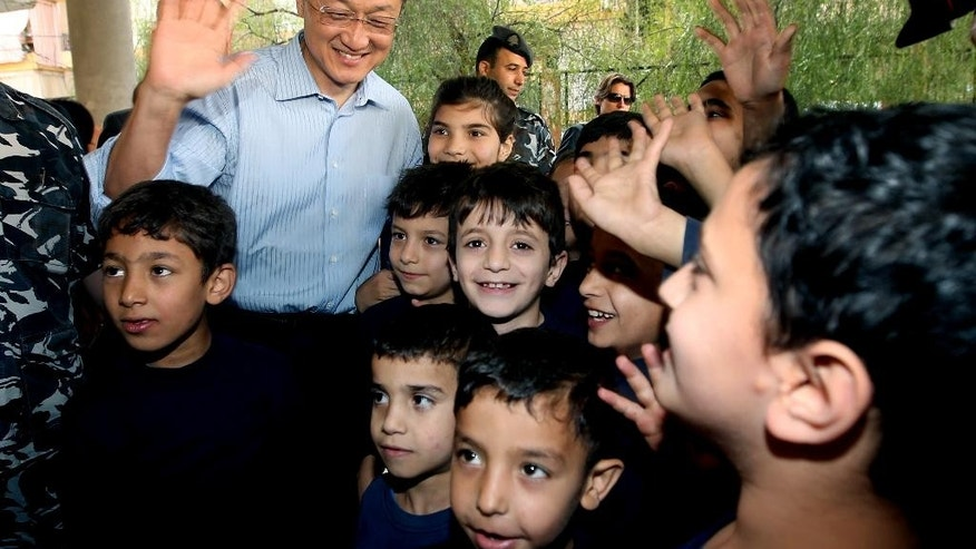 World Bank President Jim Yong Kim, left, waves as he stands next to Syrian refugee students, at a Lebanese public school, in Burj Hammoud area, east Beirut, Lebanon, Tuesday, June 3, 2014. Kim is on an official visit to Lebanon aimed at supporting the tiny Arab country which is hosting over a million Syrian refugees. (AP Photo/Hussein Malla)
