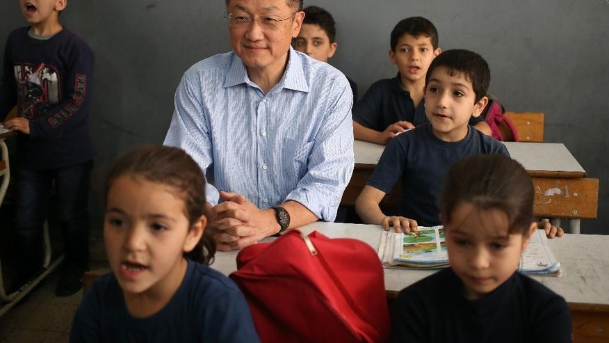 World Bank President Jim Yong Kim, center, sits in a classroom with Syrian refugee students, at a Lebanese public school, in Burj Hammoud area, east Beirut, Lebanon, Tuesday, June 3, 2014. Kim is on an official visit to Lebanon aimed at supporting the tiny Arab country which is hosting over a million Syrian refugees. (AP Photo/Hussein Malla)