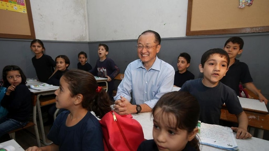 World Bank President Jim Yong Kim, center, sits in a classroom with Syrian refugee students at a Lebanese public school, in the Burj Hammoud area of east Beirut, Lebanon, Tuesday, June 3, 2014. Kim is on an official visit to Lebanon aimed at supporting the tiny Arab country which is hosting over a million Syrian refugees. (AP Photo/Hussein Malla)