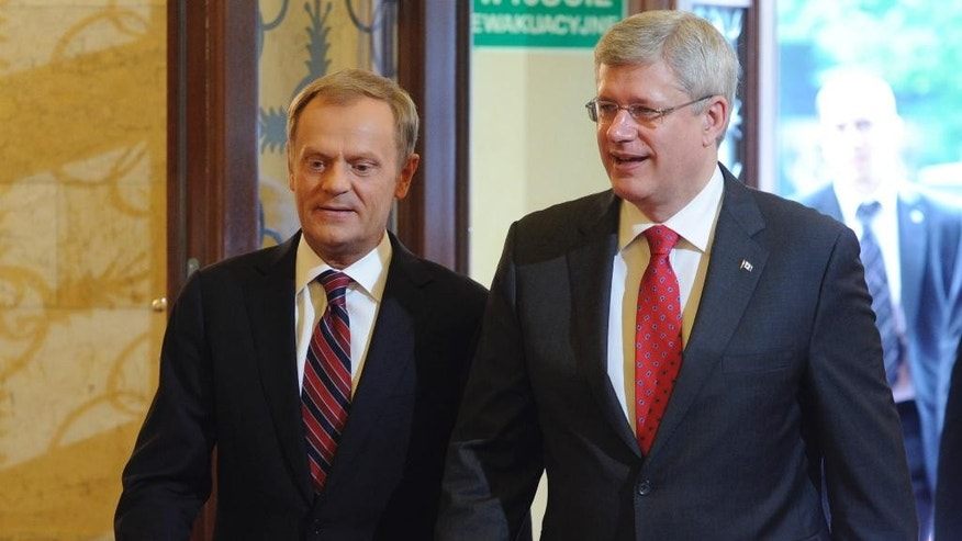 Canada's Prime Minister Stephen Harper, right, and his Polish counterpart Donald Tusk walk for their talks in Warsaw, Poland, Wednesday, June 4, 2014. (AP Photo/Alik Keplicz)