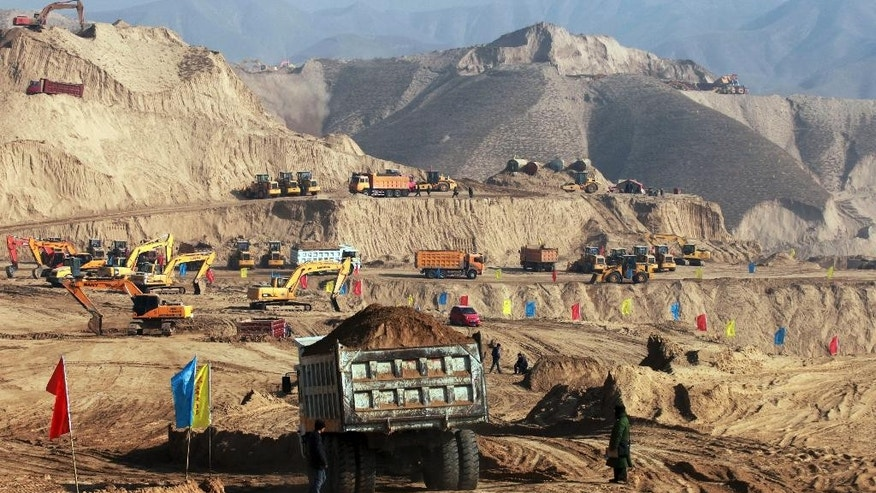 In this photo taken Monday Dec. 10, 2012, earth moving vehicles  are seen at work at a site in Baidaoping area in Lanzhou in northwest China's Gansu province.  China's campaign to shave off mountaintops and fill in valleys to make way for cities may come at too high a price in the pollution, erosion and flooding unleashed by the unprecedented redistribution of earth, Chinese researchers warned Thursday June 5, 2014. (AP Photo) CHINA OUT