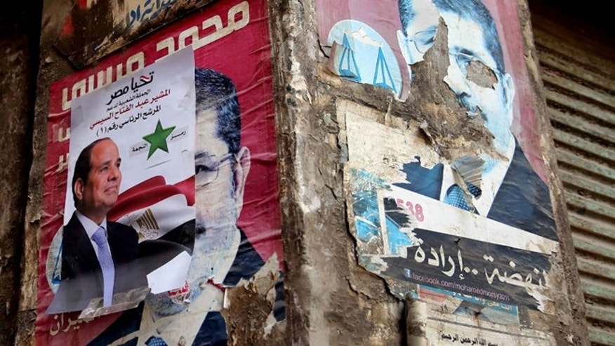 May 26, 2014: Defaced presidential campaign posters of ousted Islamist President Mohammed Morsi are seen on a wall, background, with a presidential campaign poster of retired Field Marshal Abdel-Fattah el-Sissi, center, on top during the first day of presidential elections in Cairo, Egypt.