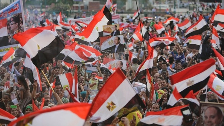 June 3, 2014: Supporters of Abdel-Fattah el-Sissi, the nations former military chief, raise his posters and national flags during a celebration at Tahrir Square in Cairo, Egypt. (AP)