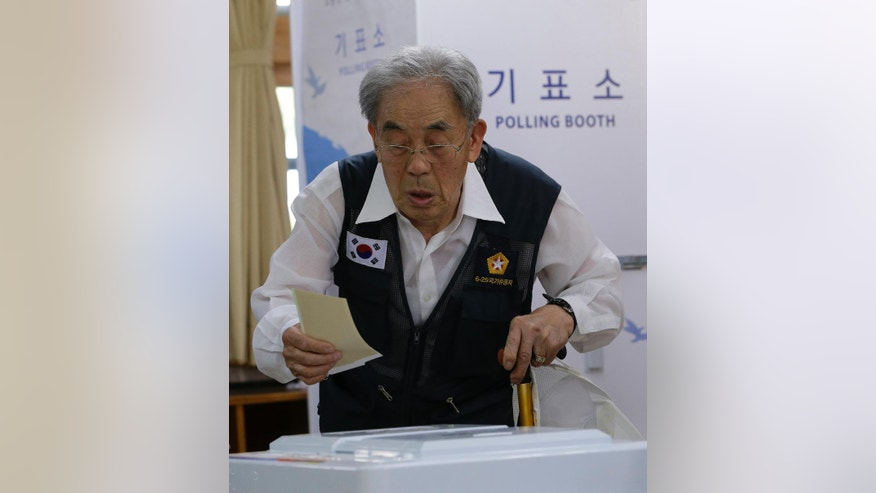 A Korean War veteran casts his ballot for local elections at a polling station in Seoul, South Korea, Wednesday, June 4, 2014. South Koreans began voting Wednesday in local elections seen as a test of how the public feels about President Park Geun-hye's handling of April's deadly ferry sinking. (AP Photo/Lee Jin-man)
