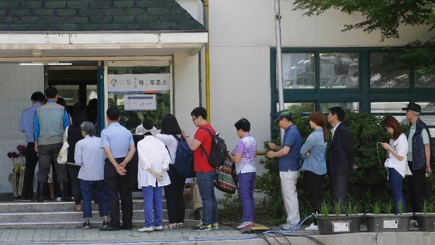 Residents queue for their votes for local elections at a polling station in Seoul, South Korea, Wednesday, June 4, 2014. South Koreans began voting Wednesday in local elections seen as a test of how the public feels about President Park Geun-hye's handling of April's deadly ferry sinking. (AP Photo/Lee Jin-man)