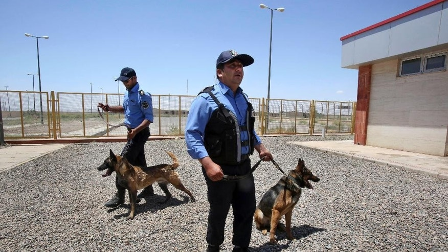 In this Sunday, June 1, 2014 photo, two Iranian custom officers hold their drug-sniffing dogs at Iran's Dogharoun custom's house on border with Afghanistan, near Taibad in eastern Iran. In the face of Afghanistan's unprecedented boom in opium production, neighboring Iran is trying to baton down its border to slow down smuggling, building moats, walls and other large-scale projects. Iran spent more than $26 million last year alone on the border projects which also include large embankments, new border posts and lengths of barbed wire along parts of its 2,000-kilometer (1,200-mile) border with Afghanistan and Pakistan. (AP Photo/Vahid Salemi)