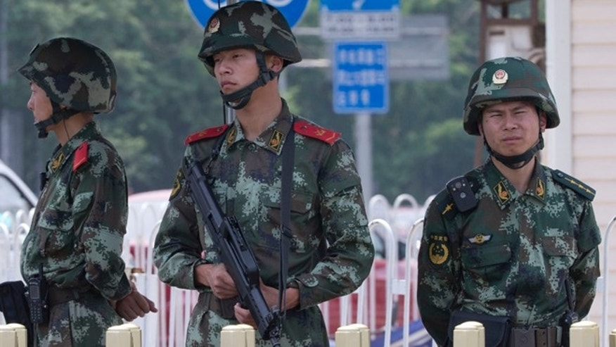 June 4, 2014: Chinese paramilitary policemen man a security checkpoint on Tiananmen Square in Beijing. Authorities in Beijing blanketed the city center with heavy security Wednesday on the 25th anniversary of the bloody military suppression of pro-democracy protests centered on Tiananmen Square.