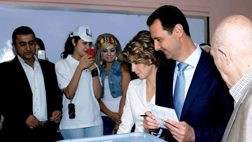 In this photo released by the Syrian official news agency SANA, Syrian President Bashar Assad, second right, casts his vote as Syrian first lady Asma Assad, stands next to him at a polling station, in Damascus, Syria, Tuesday, June 3, 2014. Thousands of Syrians lined up outside polling centers in government-controlled areas around the country to vote Tuesday in the presidential election that Assad is widely expected to win but which has been denounced by critics as a sham. (AP Photo/SANA)