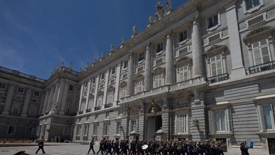 "A civil guard, bottom left watches a musical band walk past during the traditional 'Changing of the Guard' ceremony at the Royal Palace in Madrid,  Spain, Wednesday, June 4, 2014. The cabinet of Spanish Prime Minister Mariano Rajoy has approved a proposal for emergency legislation that allows King Juan Carlos to abdicate and hand over his duties to Crown Prince Felipe. Juan Carlos is widely respected for leading Spain's transition from dictatorship to democracy and staring down a 1981 coup attempt, but was hit hard by royal scandals over the last several years. He announced Monday he was abdicating because his son is ready for the job and because Spain needs a ""new era of hope."" (AP Photo/Paul White)"