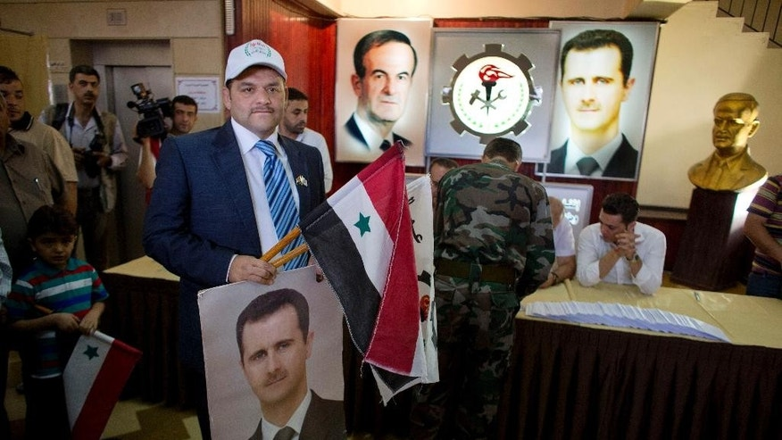 A man holds a portrait of President Bashar Assad and a national flag at a polling station in Damascus, Syria, Tuesday, June 3, 2014. Polls opened in government-held areas in Syria amid very tight security Tuesday for the country's presidential election, a vote that President Bashar Assad is widely expected to win. (AP Photo/Dusan Vranic)