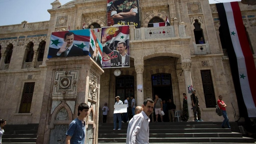 An old trains station is decorated with posters showing President Bashar Assad, in Damascus, Syria, Tuesday June 3, 2014. Polls opened in government-held areas in Syria amid very tight security Tuesday for the country's presidential election, a vote that President Bashar Assad is widely expected to win. (AP Photo/Dusan Vranic)