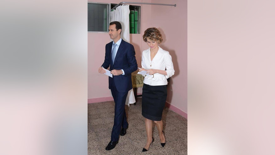 In this photo released by the Syrian official news agency SANA, Syrian President Bashar Assad, left, and first lady Asma Assad, right, leave a voting booth to cast their vote at a polling center, in Damascus, Syria, Tuesday June 3, 2014. Thousands of Syrians lined up outside polling centers in government-controlled areas around the country to vote Tuesday in the presidential election that Bashar Assad is widely expected to win but which has been denounced by critics as a sham. (AP Photo/SANA)