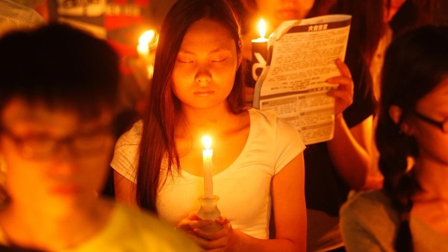 A woman closes her eyes as she joins tens of thousands of people attending a candlelight vigil at Victoria Park in Hong Kong Wednesday, June 4, 2014 to mark the 25th anniversary of the June 4th Chinese military crackdown on the pro-democracy movement in Beijing. (AP Photo/Kin Cheung)
