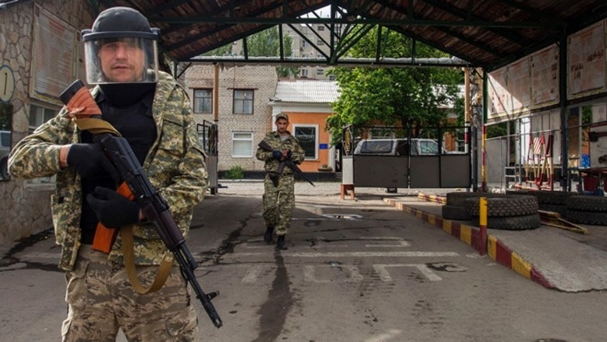 June 4, 2014: Pro-Russian armed men walk in an entrance to a border guards base, which they seized, on the outskirts of Luhansk, Ukraine. Pro-Russian insurgents in eastern Ukraine have taken two government bases in battles around Luhansk, seizing quantities of ammunition and explosives from a border guards post and taking another installation after National Guard forces ran out of ammunition.