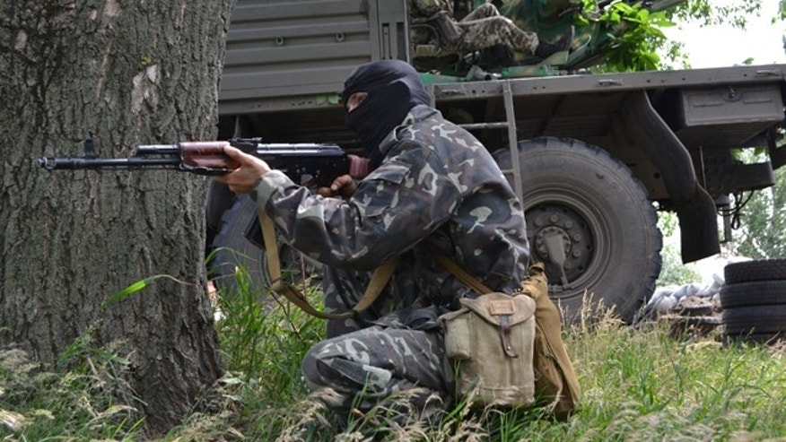 June 3, 2014: A Pro-Russian militant takes a position to fight against Ukrainian government forces outside Slovyansk, eastern Ukraine. (AP Photo/Andrei Petrov)
