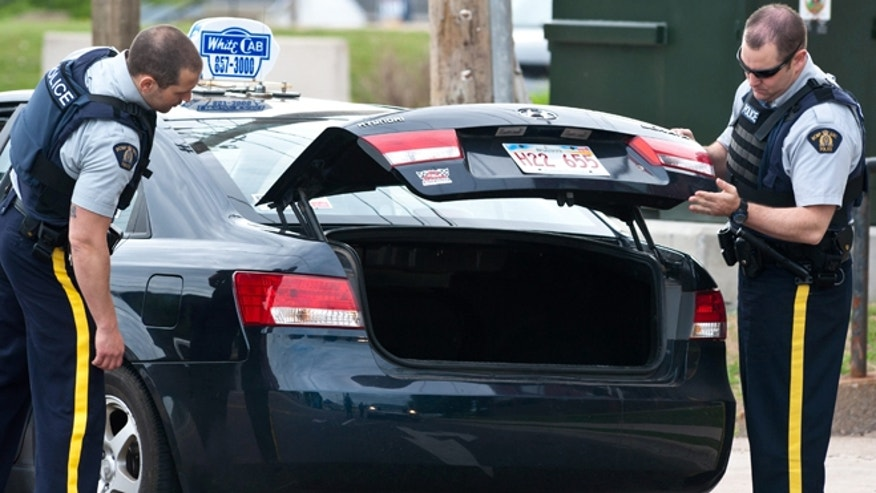 June 5, 2014: Royal Canadian Mounted Police check the trunk of a taxi at a roadblock in Moncton, New Brunswick. A RCMP manhunt for a gunman suspected of killing three Mounties and wounding two others passed the 12-hour mark Thursday in Moncton as a large section of the New Brunswick city was under a virtual siege.