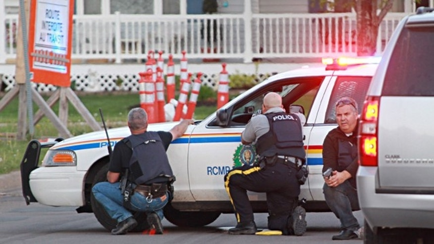 June 4, 2014: Police officers take cover behind their vehicles in Moncton, New Brunswick. Three police officers were shot dead and two others injured Wednesday in the east coast Canadian province of New Brunswick, officials said, and authorities were searching for a suspect. (AP Photo/Moncton Times & Transcript, Ron Ward via The Canadian Press)