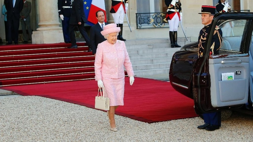French President Francois Hollande, back, looks on as Britain's Queen Elizabeth II walks to her car after their meeting at the Elysee Palace in Paris, Thursday, June 5, 2014. The commemorations the 70th anniversary of D-Day culminate on June 6, where U.S. President Barack Obama, French president Francois Hollande and Britain's Queen Elizabeth II will gather in Normandy to remember the more than 9,000 Allied soldiers killed or wounded that day. (AP Photo/Francois Mori)