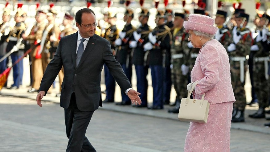 Britain's Queen Elizabeth is accompanied by France's President Francois Hollande as she attends a wreath-laying ceremony at the Arc de Triomphe in Paris, France, Thursday, June 5, 2014. The Queen arrived in Paris to start a three-day state visit and participate in ceremonies commemorating the D-day landings in Normandy. (AP Photo/Charles Platiau,pool)