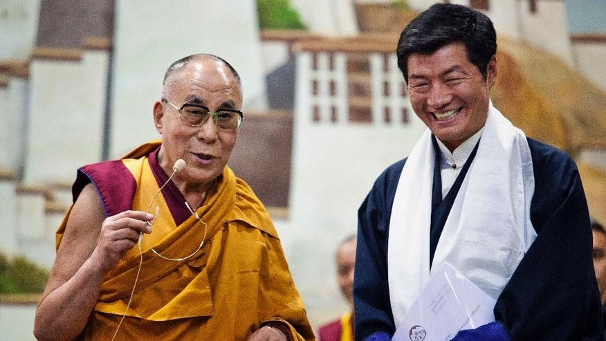 "Lobsang Sangay, prime minister of the Tibetan government-in-exile, right, smiles as he listens to spiritual leader the Dalai Lama at the Tibetan Children's Village School in Dharmsala, India, Thursday, June 5, 2014. The prime minister has reaffirmed Tibet's commitment to the ""Middle Way"" approach, a way of engaging China in dialogue to achieve a meaningful autonomy for Tibetans within the country. The ""Middle Way Approach"" was proposed by the Dalai Lama and adopted as an official policy by the exiled parliament in 1997. (AP Photo/Ashwini Bhatia)"