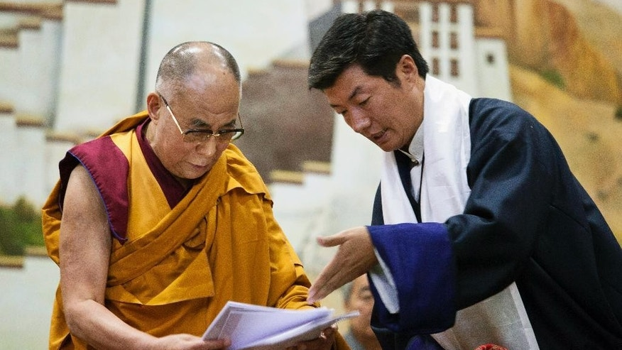 "Lobsang Sangay, prime minister of the Tibetan government-in-exile, right, presents a document to spiritual leader the Dalai Lama at the Tibetan Children's Village School in Dharmsala, India, Thursday, June 5, 2014. The prime minister has reaffirmed Tibet's commitment to the ""Middle Way"" approach, a way of engaging China in dialogue to achieve a meaningful autonomy for Tibetans within the country. The ""Middle Way Approach"" was proposed by the Dalai Lama and adopted as an official policy by the exiled parliament in 1997. (AP Photo/Ashwini Bhatia)"