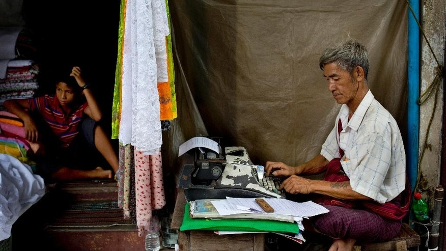 "In this May 22, 2014 photo, Aung Myint types a document from his sidewalk stand in Yangon, Myanmar. The 67-year-old insists typewriters still have some advantages over computers. ""You don't need to waste time with printing,"" he says, fingers flying high over the keys and then hammering down as he speaks. ""And if you make a mistake, you can just erase it and type over it. It's easier."" (AP Photo/Gemunu Amarasinghe)"