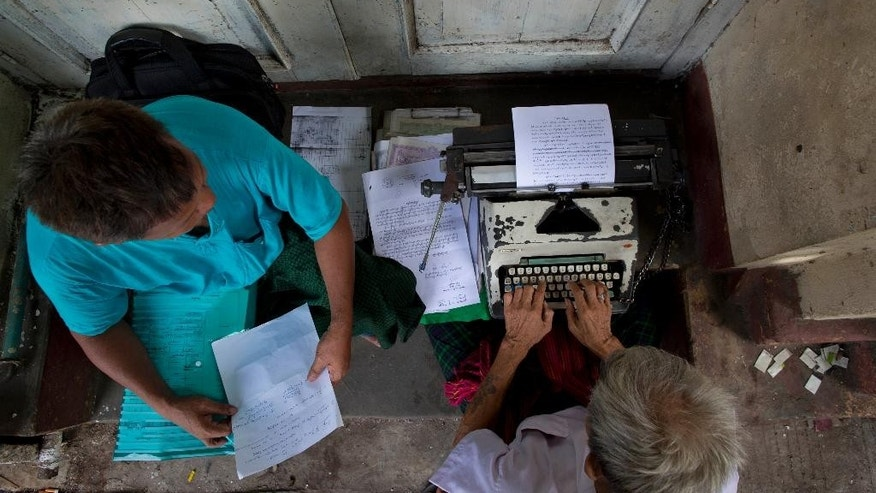 In this May 28, 2014 photo, Aung Myint types a document for a waiting customer on a sidewalk in Yangon, Myanmar.  Computer shops have sprouted up on pretty much every block in Yangon, but there are those that still feel a document lacks an authentic air unless it's pulled from the roll of a manual typewriter. (AP Photo/Gemunu Amarasinghe)