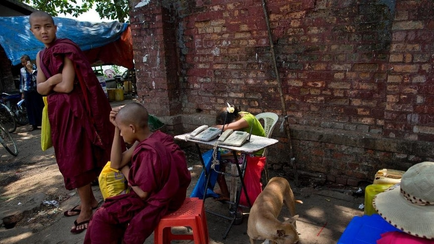 In this April 24, 2014 photo, Buddhist monks hang out near a telephone stand in Myanmar's commercial capital of Yangon, as the vendor takes an afternoon nap. Though foreign investors have flocked to the country since it opened up after a half-century of military rule, the vast majority of the people have yet to benefit from the development boom. (AP Photo/Gemunu Amarasinghe)
