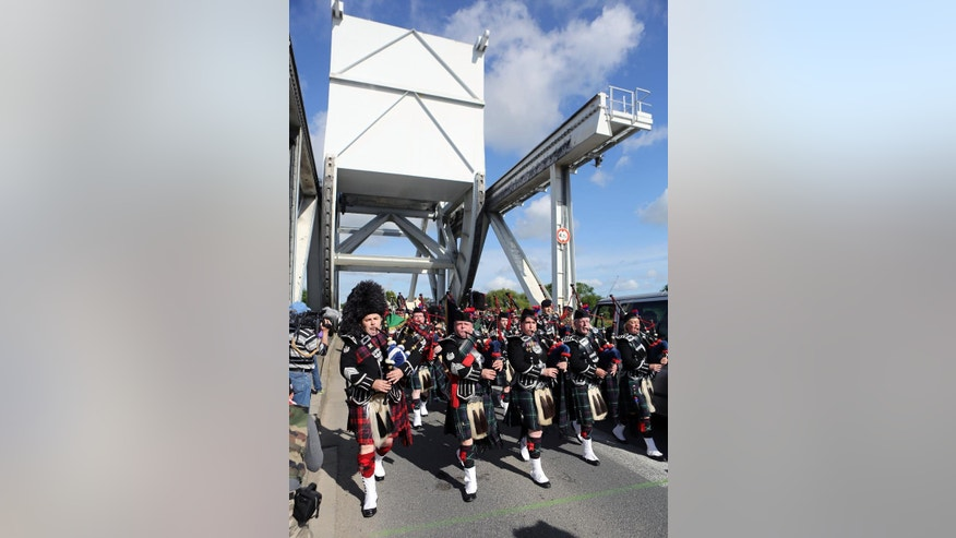 June 5, 2014: A Scottish pipe band  parades on Pegasus Bridge in Benouville western France, as part of the commemoration of the 70th anniversary of the D Day. World leaders and veterans prepare to mark the 70th anniversary of the invasion this week in Normandy.