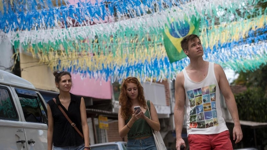 In this May 23, 2014, photo, tourists walk on a street decorated for the upcoming World Cup, in Rio de Janeiro, Brazil. Visitors to Brazil will find the land of soccer, sun and surprisingly sky-high prices. It's not just hotels and flights that are wallet busters. It's the $35 pepperoni pizza, the $10 cocktails and $17 cheeseburgers, standard prices around the country. (AP Photo/Silvia Izquierdo)