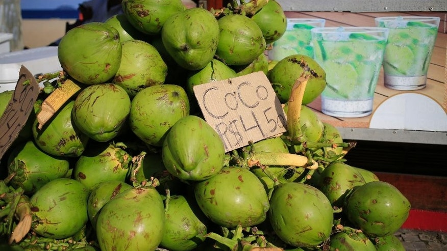 Coconuts are on display for sale at a kiosk on the Barra de Tijuca beach in Rio de Janeiro, Brazil, Tuesday, June 3, 2014. It's not just the hotels and flights that will break wallets. It's the $10 caipirinhas, the $17 cheeseburgers or that $35 pepperoni pizza. If you hit the beach in Rio de Janeiro, you'll likely sip on a $3 coconut and on the way back to your overpriced hotel, you'll ride in public transportation that's more costly than London. (AP Photo/Hassan Ammar)