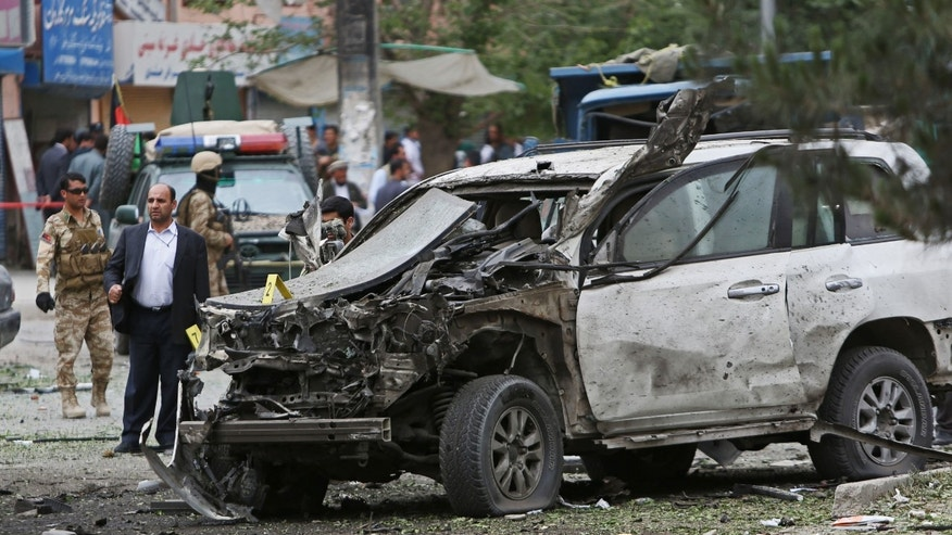 June 6, 2014 - Afghan security forces investigate the site of a suicide attack that struck the convoy of presidential candidate Abdullah Abdullah in Kabul, Afghanistan. 2 blasts struck a convoy carrying Abdullah after a campaign event, killing several civilians but leaving the candidate unharmed, officials said.