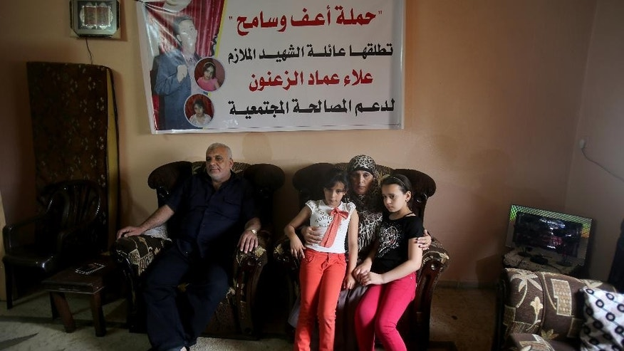 In this June 3, 2014 photo, Imad and Rawda Zanoun sit with their grandchildren Rawda and Farah in their living room beneath a memorial banner for the girls' father, Alaa Eldin, who was killed in a 2007 fight between Hamas and Fatah days before the Hamas take over in Gaza City. The Palestinian unity government has settling demands of justice for hundreds killed and wounded in fighting, that culminated in the 2007 Hamas takeover of the Gaza Strip, ahead of them. (AP Photo/Hatem Moussa)